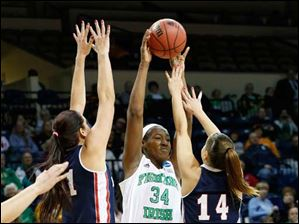 Notre Dame's Markisha Wright (34), passing over the arms of RMU's Artemis Spanou, left, and Ashley Ravelli.