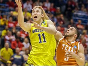 Michigan's Nik Stauskas, who had 17 points, is fouled by Texas' Javan Felix in an NCAA tournament game in Milwaukee. The Wolverines will play the winner of today's Tennessee-Mercer game.