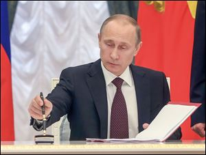 Russian President Vladimir Putin signs bills making Crimea part of Russia.