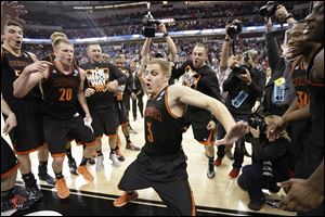 Mercer guard Kevin Canevari (3) dances with teammates after the Bears stunning upset of Duke.
