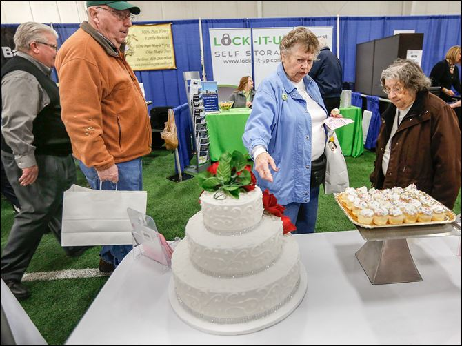 23n1showcase-2 Holland residents Dubby Ruckman, second from right, and Ada Mae Schooner, right, admire a three-tier wedding cake from Eston's Bakery during the Showcase Sylvania Expo at Tam-O-Shanter.