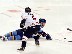 The Walleye's Jesse Messier tries to recover the puck while the Gladiators' Josh Currie looks back.