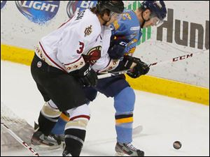 Toledo's Kyle Bodie and the Gladiators' Marshall Everson fight to get to the puck.