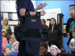 Lake Township Officer Jon Penny holds a human kevlar vest as he speaks with a crowd of children and their parents about efforts to purchase similar vests for local police dogs.
