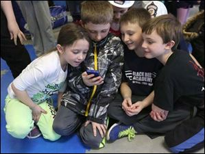 Jera Harrington, 7, left, and her brothers Tristian, 9, center left, and Logan, 10, right, along with Evan McCormick, 8, right, watch an instant replay of Lake Township Officer Jon Penny being hit with a stun gun.