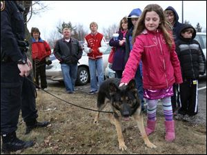 Adriana Persiani, 9, gives the Perrysburg Township police dog X, a three-year-old German Shepherd, a pat.