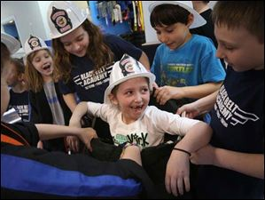 Jera Harrington, 7, center, laughs as other children carry her in a pair of firefighter's pants.