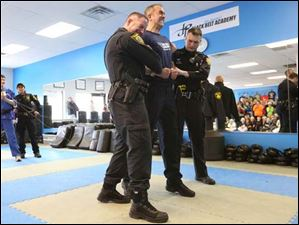Lake Township officer Jon Penny, center, reacts to being hit with voltage from a stun gun.