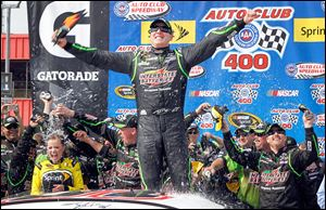 Kyle Busch celebrates as his team drenches his wife, Samantha Busch, left, in victory circle after his win.