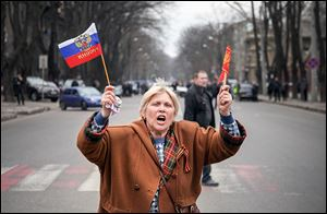 A pro-Russian activist waves Russian and former Soviet flags with a ribbon symbolizing the Soviet victory in WWII, during a rally against usurpation of power and political repression.