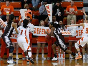 BGSU cheerleaders hold defense signs as St. Bonaventure's Imani Outlaw dribbles between BGSU's Jasmine Matthews, 1, and Miriam Justinger during the 2nd half.