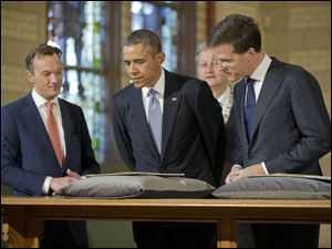 U.S. President Barack Obama, center, views the Act of Abjuration, widely considered to be the source document for the U.S. Declaration of Independence, during a tour of the Rijksmuseum with Museum Director Wim Pijbes, left, Prime Minister of the Netherlands Mark Rutte, right, and Mayor of Amsterdam Eberhard van der Laan today in Amsterdam.