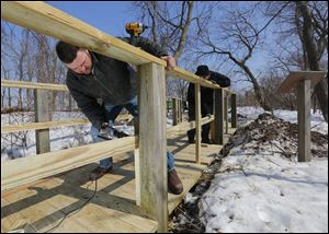 Todd Ebersole, left, and Brian Pritchard, both of Todd Hunt Contracting, Marion, Ohio, install a new railing on the boardwalk at Magee Marsh near Oak Harbor, Ohio. The 25-year-old boardwalk's deteriorating condition makes the structure a safety hazard, the Friends of Magee Marsh said.