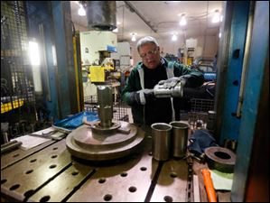 Daniel Tenney, an employee with Toledo Metal Spinning, works to make a steel blender cup.