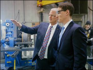 Eric Fankhauser, left, vice president of Toledo Metal Spinning, gives Ohio Treasurer Josh Mandel, right, a tour of the company Monday.