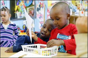 Regal Ellis, 4, and Jailan Moore, 3, right, help each other with their writing exercise during an afternoon Head Start class at the Frederick Douglass Community Center.