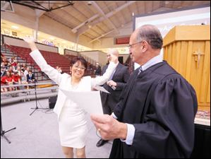 Arlene Selario Gay, left, raises her arms in jubilation with Judge Jack Zouhary, right, after becoming a US citizen.