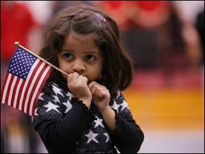 Aashna Lalla, 3, holds the flag and watches her father Anish Lalla, not pictured, originally from India, become a US citizen.