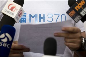 A representative of relatives of Chinese passengers onboard Malaysia Airlines Flight 370, center, makes an announcement to journalists prior to a briefing with Malaysian officials at a hotel in Beijing, China. About two-thirds of the missing, 239 people onboard, are Chinese, and their relatives have lashed out at Malaysia for essentially declaring their family members dead without any physical evidence of the plane's remains.
