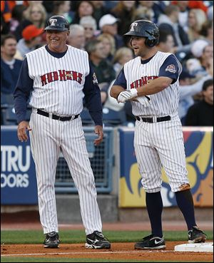 Mud Hens manager Larry Parrish is all smiles as Michael Bertram reaches third base after a triple in a 2010 game.