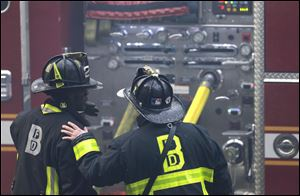 A firefighter places his hand on the shoulder of another.