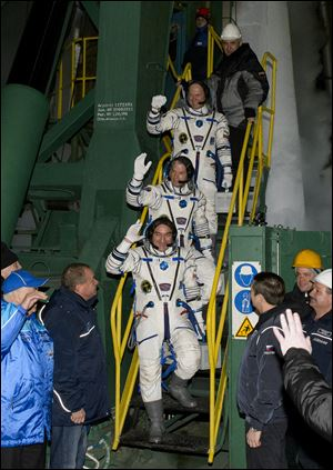 Expedition 39 Soyuz commander Aleksander Skvortsov, of the Russian Federal Space Agency (Roscosmos), followed by, flight engineer Steve Swanson of NASA, middle, and flight engineer Oleg Artemyev of Roscosmos, wave farewell prior to boarding the Soyuz rocket today.