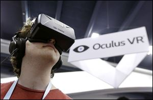 Peter Mason tries the Oculus virtual reality headset at the Game Developers Conference 2014 in San Francisco. Facebook CEO Mark Zuckerberg believes Oculus can be a key tech platform of the future.