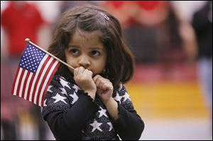 Aashna Lalla, 3, watches as her father, Anish Lalla, originally from India, becomes a U.S. citizen.