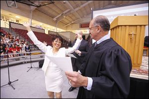 Arlene Selario Gay raises her arms in jubilation after becoming a U.S. citizen during a naturalization ceremony at Central Catholic High School presided over Wednesday by Judge Jack Zouhary.