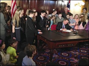 Ohio Gov. John Kasich signs a bill to grant school districts additional calamity days before a group of students at the Statehouse in Columbus.