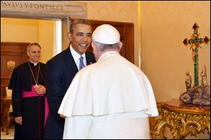 Pope Francis welcomes President Obama as Archbishop George Gaenswein, background left, looks on, at the Vatican today.