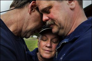 Darrington Fire District 24 volunteer firefighters, Jeff McClelland , left, Jan McClelland, center, and Eric Finzimer embrace each other Wednesday in Darrington, Wash., after saying a prayer for the victims and survivors of the massive mudslide.