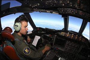 Flight Lt. Russell Adams looks out from the cockpit on board a Royal Australian Air Force AP-3C Orion Wednesday, during a search for the missing Malaysia Airlines Flight 370 in the southern Indian Ocean.