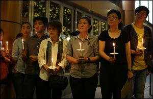 People hold candles during a ceremony in memory of passengers on board the missing Malaysia Airlines Flight MH370 in Kuala Lumpur, Malaysia Thursday.