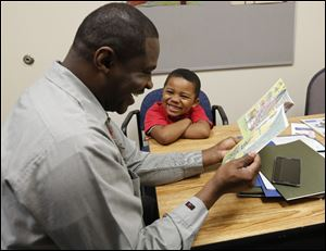 David Bush, from the Toledo-Lucas County Public Library, helps Devin Burke read 'The Boy Who Wouldn't Share' as part of the Real Men READ-y program, which gives black boys a role model.