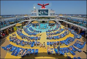 Vacationers aboard the Carnival Breeze sunbathe while viewing a movie on a 270-square-foot screen. Lines are looking for ways to lure the 200 million Americans who have never taken a cruise.