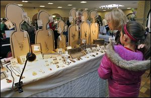 Kamryn Phillips, 11, and her aunt Lynn Witte look at jewelry from the Spare Parts booth. The free event at Lourdes University is part of its celebration of National Women's History Month and recognizes women in the visual and performing arts through a juried show and sale.