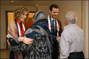 First lady Asma Assad, left background, and Syrian President Bashar Assad, right background, shaking hands with Syrian teachers in Damascus earlier this month.