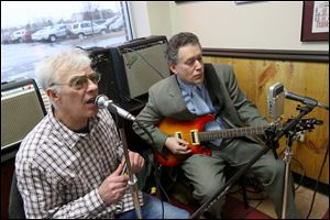 Tim Healy, left, sings while Art Schlosser, both of West Toledo, right, plays as the pair preform at the Maumee restaurant Deet's BBQ. Healy and Schlosser make up the duet Slim & Slam.
