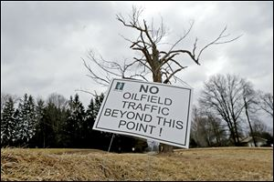 A sign near a gas well drilling site is visible near a road in Pulaski, Pa.