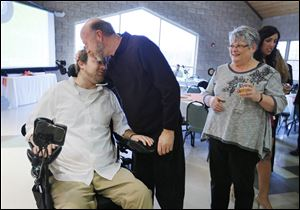 Jeremy Bigelow gets a hug from Terry Moebius at his Ain't No Mountain High Enough benefit at St. Joseph Parish in Sylvania on Saturday.  At right is Mr. Moebius's wife, Karen Moebius.
