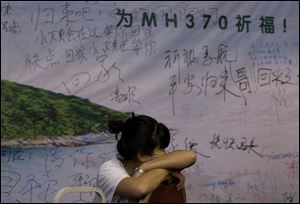 A woman, one of the relatives of Chinese passengers aboard the missing Malaysia Airlines flight MH370 takes a nap on a chair in front of a poster with writings for wishes for the passengers onboard the missing plane at a hotel in Beijing today.