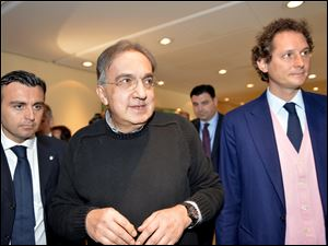 Fiat Chairman John Elkann, right, and Fiat and Chrysler CEO Sergio Marchionne arrive for a meeting with shareholders in Turin, Italy, today.