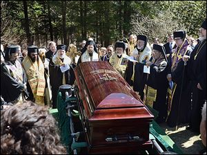 Priests gather around the casket of Metropolitan Philip Saliba at his gravesite at Antiochian Village Camp in Bolivar, Pa., before it is lowered into the ground.