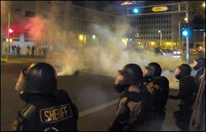 Riot police launch tear gas toward activists in downtown Albuquerque, N.M. following a 10-hour protest around the city, Sunday.