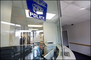 Officer James Mawer works the front desk at the newly reopened Toledo Police Department's Northwest District Substation. City leaders applauded the reopening Monday during a ribbon-cutting ceremony.