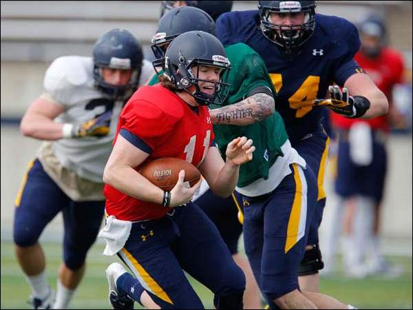 University of Toledo football player Logan Woodside (11) runs the ball during practice.