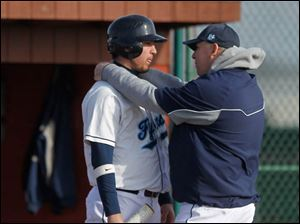 Lake's Anthony Pratt huddles with a coach prior to stepping up to the batter's box.
