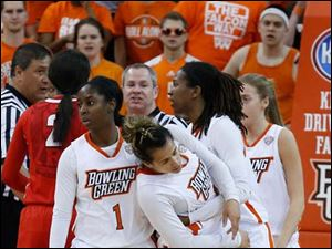 BGSU's Erica Dovovan, center, is restrained from fighting by teammates Jasmine Matthews (1) and Alexis Rogers, 2nd from right, during 2nd half.