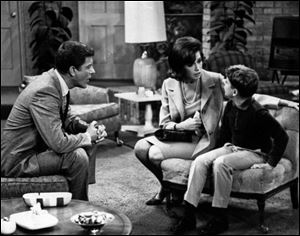 "From left, Dick Van Dyke, as Rob Petrie, and Mary Tyler Moore, as Laura Petrie, talk to Larry Matthews, who plays their son, Ritchie, on ""The Dick Van Dyke Show."" Moore is being spotlighted in a new DVD collection called ""The Dick Van Dyke Show: Classic Mary Tyler Moore Episodes."""